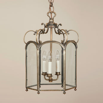 A pretty late 19th century English hexagonal brass hall lantern with arched panes and a S-scroll upper frame.