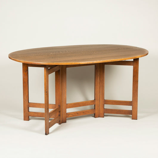 A large oval oak Cotswold gate-leg table with folding sides, early 20th century.