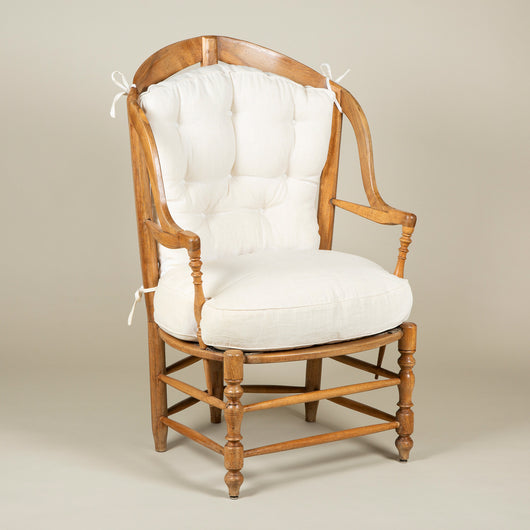 An early 19th century French provincial walnut armchair of unusual wide and shallow proportions.