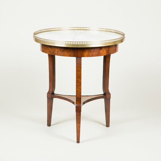 A late 19th century circular French walnut occasional table with a brass gallery and an inset marble top, circa 1900.