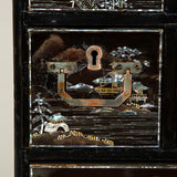 A 19th century Chinese export lacquer cabinet on a stand with mother of pearl inlay, the top opening to a dressing table, with eight drawers with inset handles.