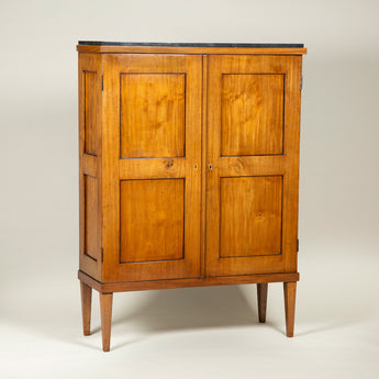 An early 19th century mahogany Biedermier cupboard with two panelled doors and a grey marble top. Probably Austrian.