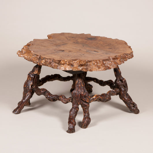 A rustic circular table made from a cross section of burr maple with knarled supports, mid-20th century.