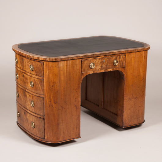 An unusual small George III mahogany kneehole desk, rectangular with drawers in the rounded sides, circa 1790.