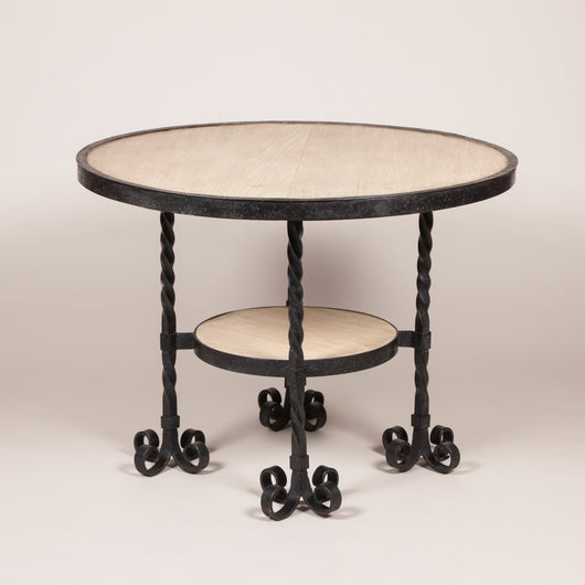 A round wrought iron table, the top and small round under-tier inset with bleached mahogany and the four legs each with four scrolled feet. Probably French, mid-20th century.