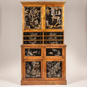 A tall cabinet in two parts with cupboards above and below an arrangement of drawers, the doors and drawers with black and gilt Chinoiserie decoration, the rest with a mottled bronze finish. Mid 20th century.
