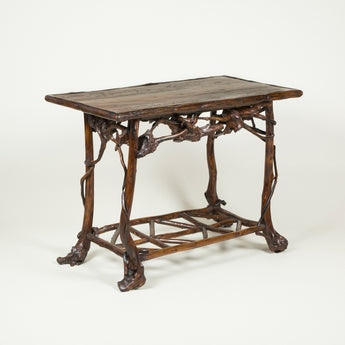 A rectangular rustic table the plank top bordered and supported by polished tree branchaes. Late 19th or early 20th century.