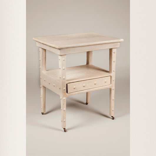 An early 20th century Continental rectangular side table with unusual white papier mache surface decoration and two tiers with a push-me-pull-me drawer under the lower one.