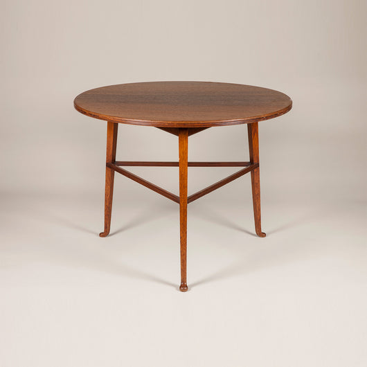 A round Aesthetic Movement rosewood table with three legs with pad feet and joined by stretchers. Howard and Sons, circa 1880.