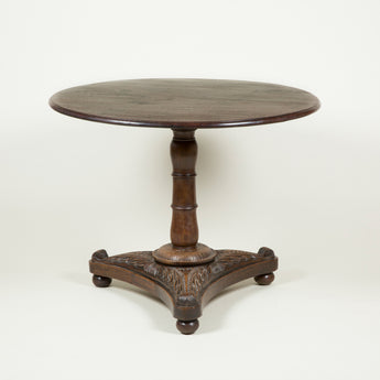 An early 19th century Anglo-Indian teak table with a round top, turned column support and leaf carved pedestal base.