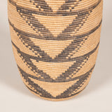 A tall African basket with a geometric pattern in black on a tan ground. Central West Africa, late 19th or early 20th Century
