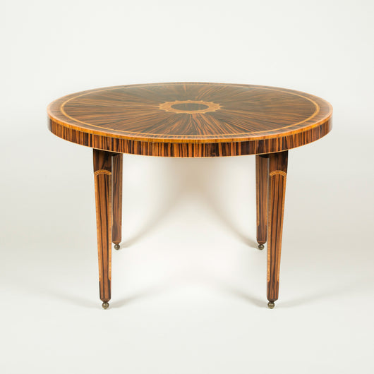 A striking round calamander wood table, the top segmentally veneered with in-laid cross banding and central motif, the four stop-chamfered legs with similar inlaid decoration. Continental, second half of the 20th century.