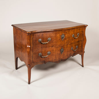 An 18th century fruitwood bombe two-drawer commode with finely cast brass handles. Continental circa 1770 possibly Dutch
