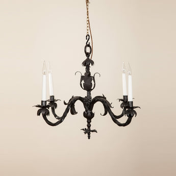 A delicate black-painted metal chandelier with four branches and wrought leaf and flower decoration. 20th century