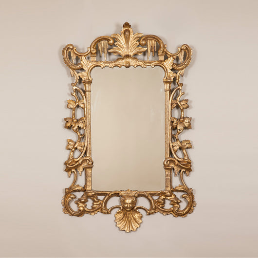 A fine early George III wall mirror, the giltwood frame with open carving of branches in leaf and rocaille work. Circa 1750, plate replaced