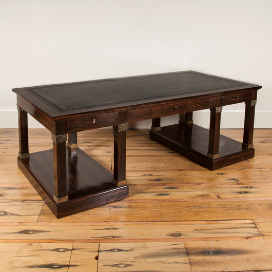 A large macassar ebony desk with a leather-lined top over three freize drawers supported by eight square section column supports with gilt brass mounts on two plinth bases. Italian, mid-20th century.