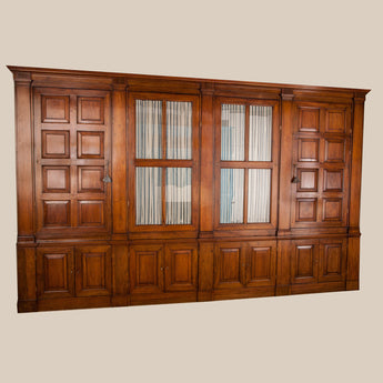 A large Italian walnut bookcase in four sections, the upper part with two glazed doors between square-panelled doors separated by pilasters, enclosing drawers and shelves. Circa 1840.
