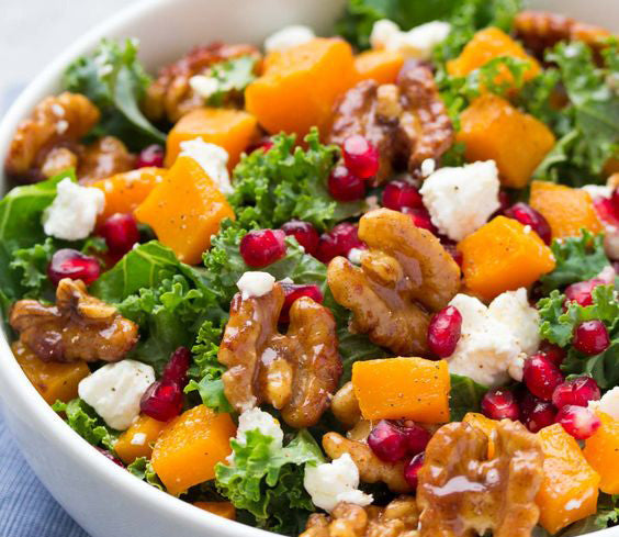 Butternut squash and pomegranate kale salad with spiced honey walnuts and a maple dressing.