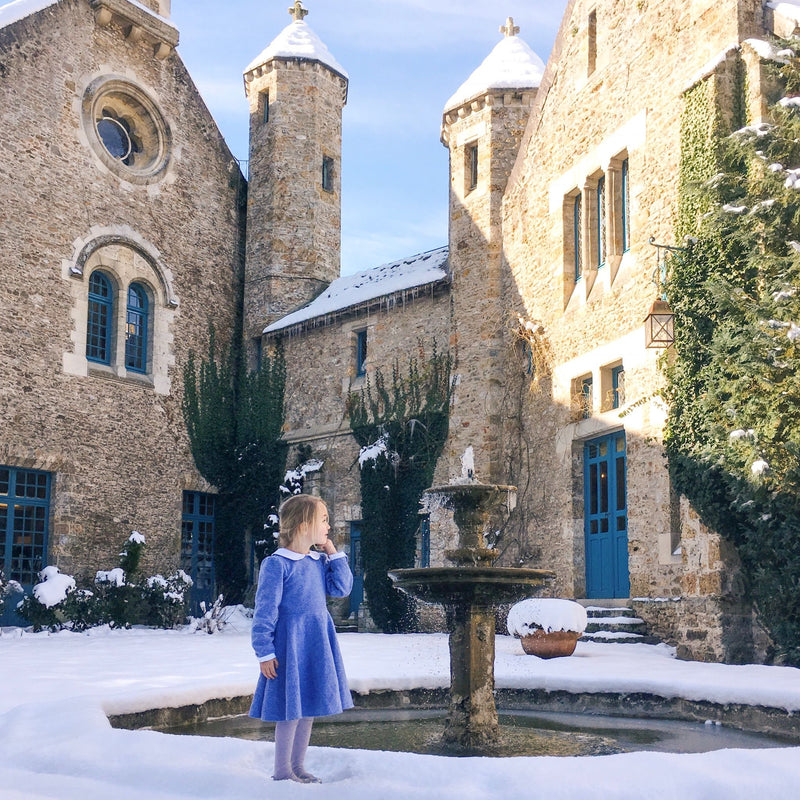 Girl wearing blue flannel dress in the snow at a castle