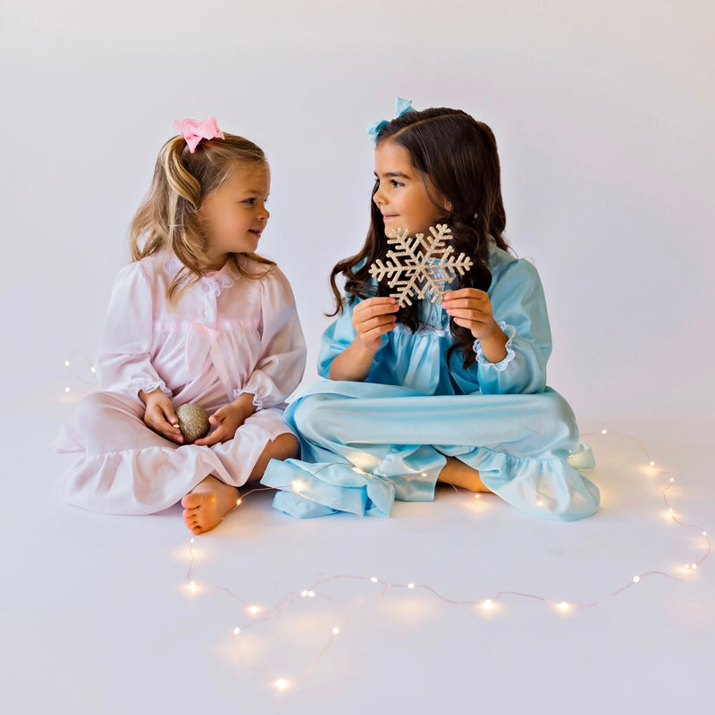 Two little girls wearing pink & blue nightgowns