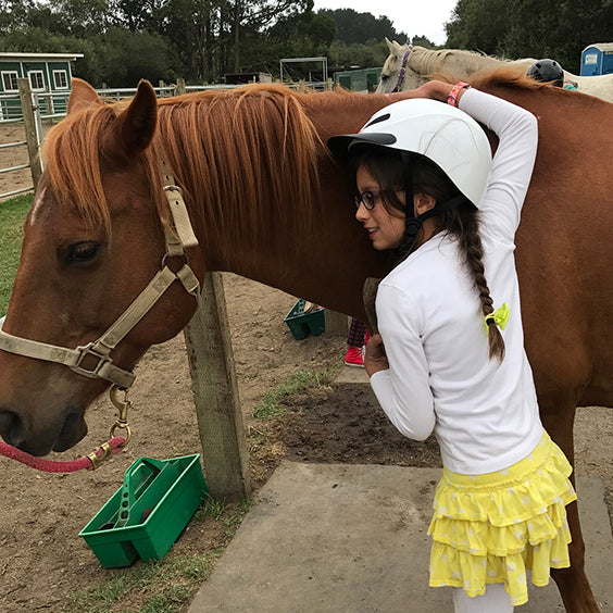 Founder's daughter hugging a horse at camp