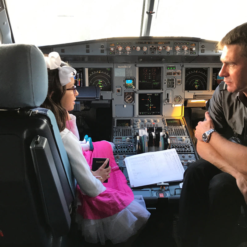 Founder daughter sitting with a pilot in the cock pit