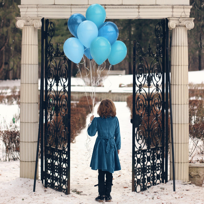 Our blue velvet dress on a girl holding balloons in the snow