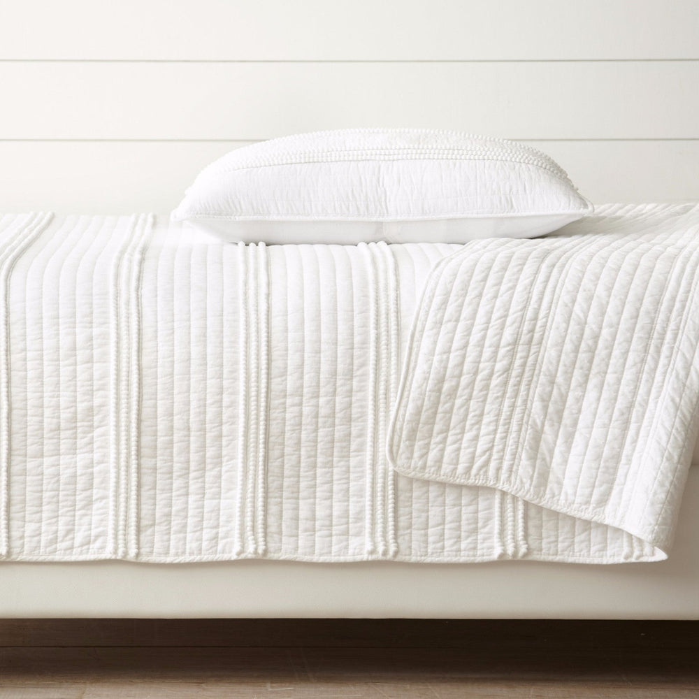 Side view of Charley Cotton Pom Pom Quilt Set in White