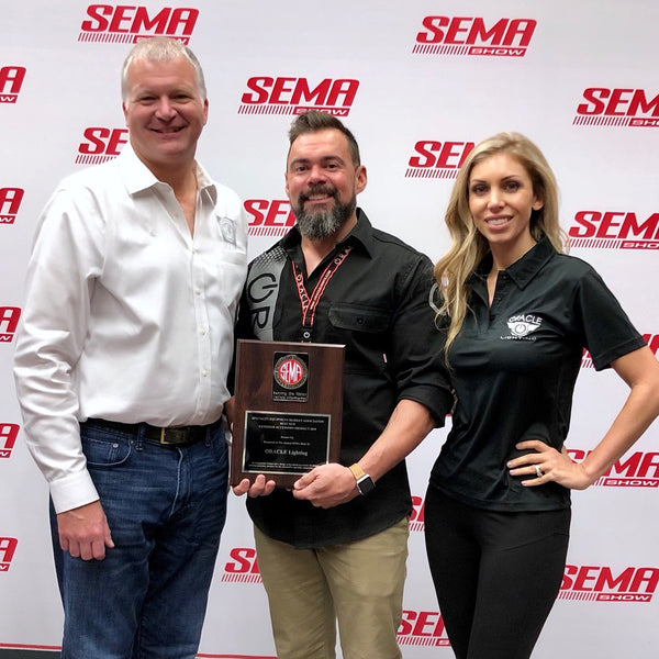 Justin & Tiffanie Hartenstein stands with unnamed to accept Oracle Lighting 2018 Global Media Award at SEMA Show