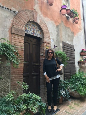 Alice Margaritelli striking a pose in front of an Italian door with hand painted motif in Deruta Italy