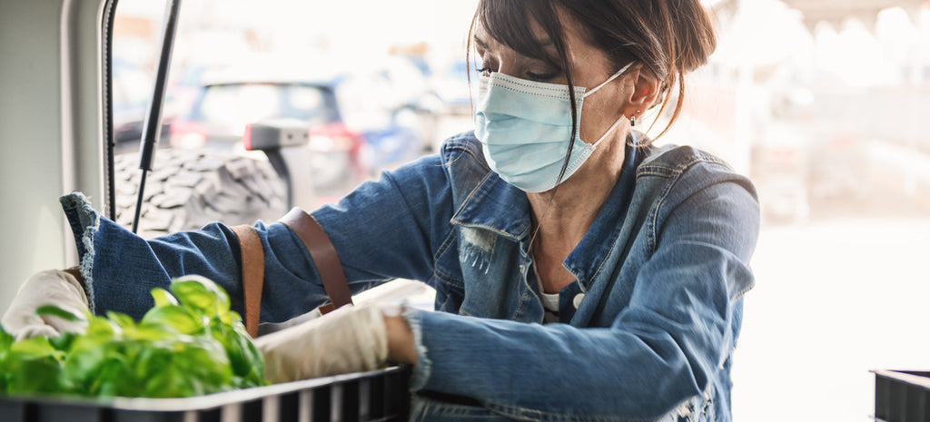 woman with mask loading groceries into car