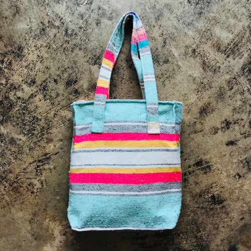 Light blue multi-colored serape style tote bag with a zippered top. Sturdy enough to carry your everyday essentials, books, laptop, or use as a fun little beach bag!