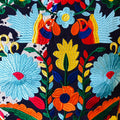 close up of a luchador pillow with blue, orange, red and yellow embroidered flowers and birds