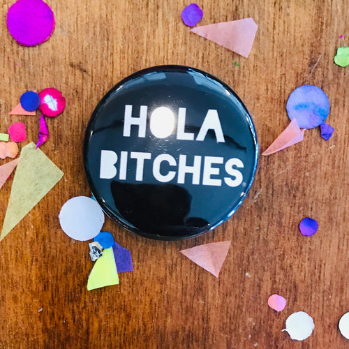 Black Hola Bitches pin-back button made by Artelexia