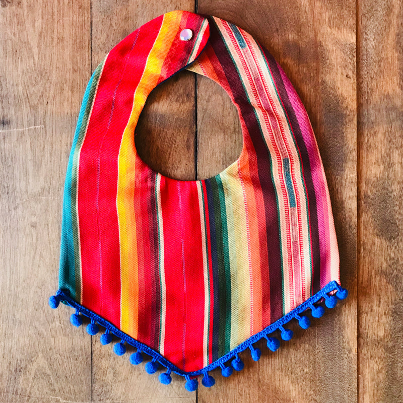 Red striped baby bibs made from authentic Mexican serape blankets with blue pompom trim