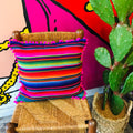 Square serape printed pillowcase with bright multi-colored stripes and hot pink pompom trim.