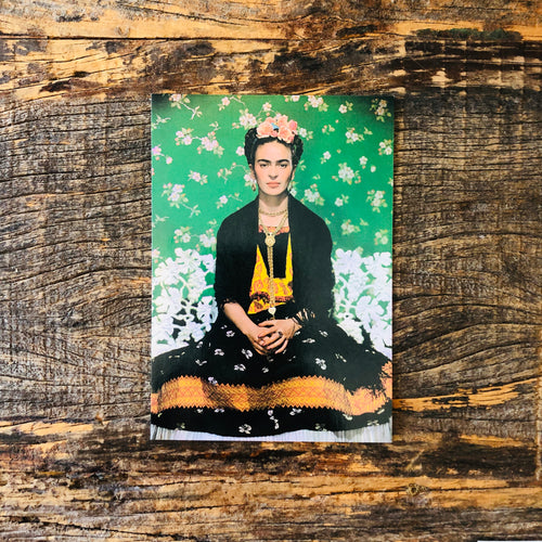 Vintage postcard of Frida Kahlo's portrait against a green floral background