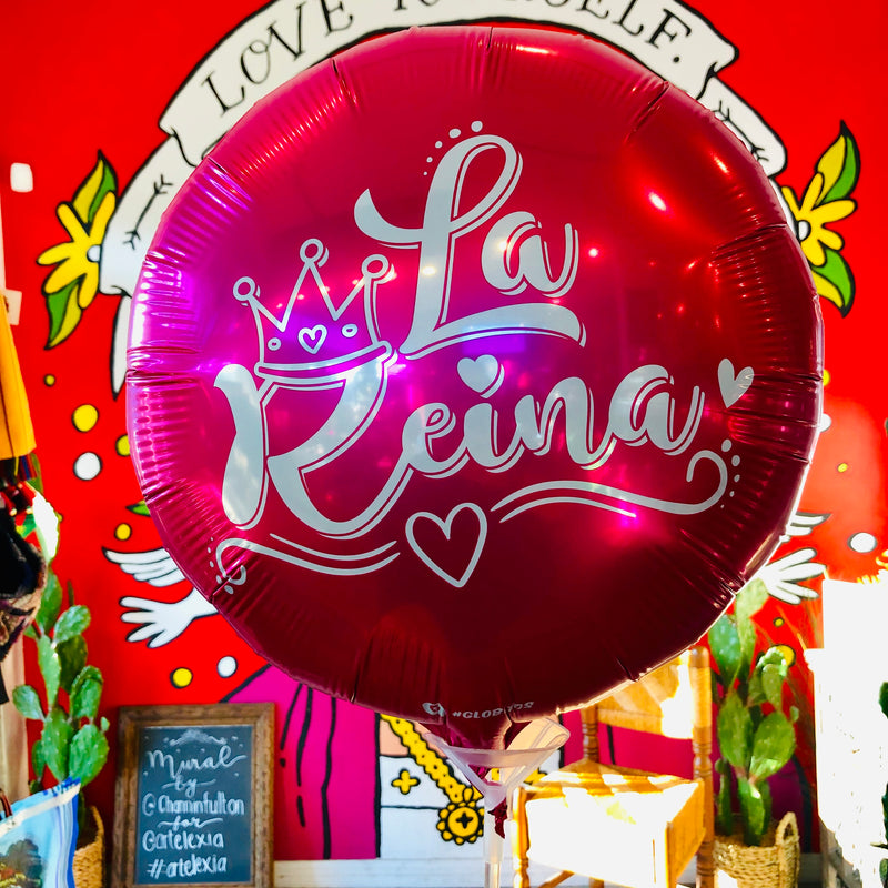 "Hot pink mylar balloon with the words ""La Reina"" and a crown detailing on it."