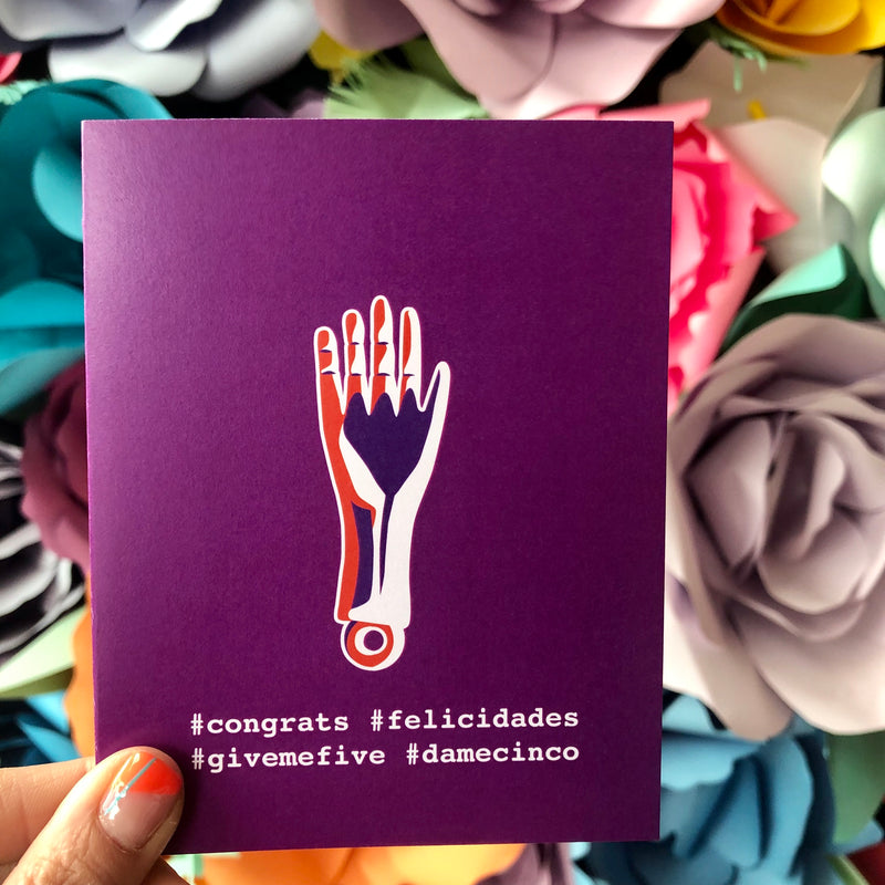 Purple greeting card with a hand milagros and hashtags on the front. The hashtags are #congrats, #felicidades, #givemefive, and #damecinco