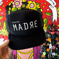 Black trucker hat with white Modern Madre lettering on the front