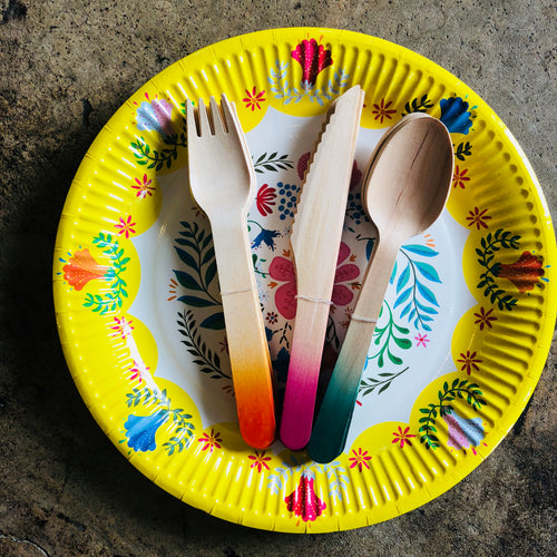 These disposable ombre wooden cutlery in orange, pink and green shades are resting on top a floral plate.