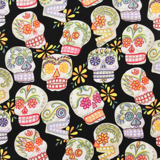 Alexander Henry Fabric with the Calaveras pattern of skulls against a black background with gold detailing