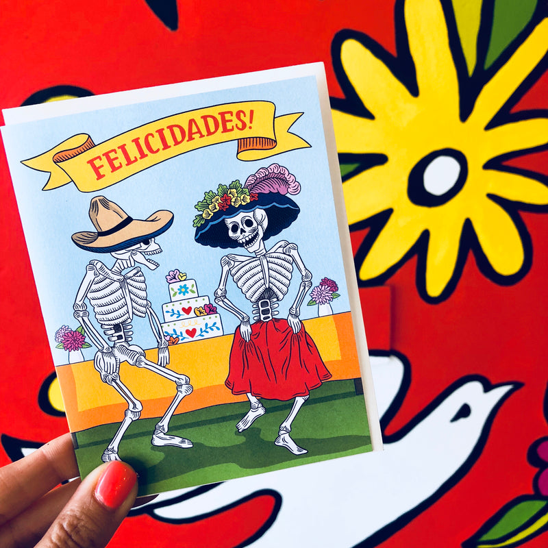 Felicidades Congratulations card are with two dancing skeletons in front of a wedding cake