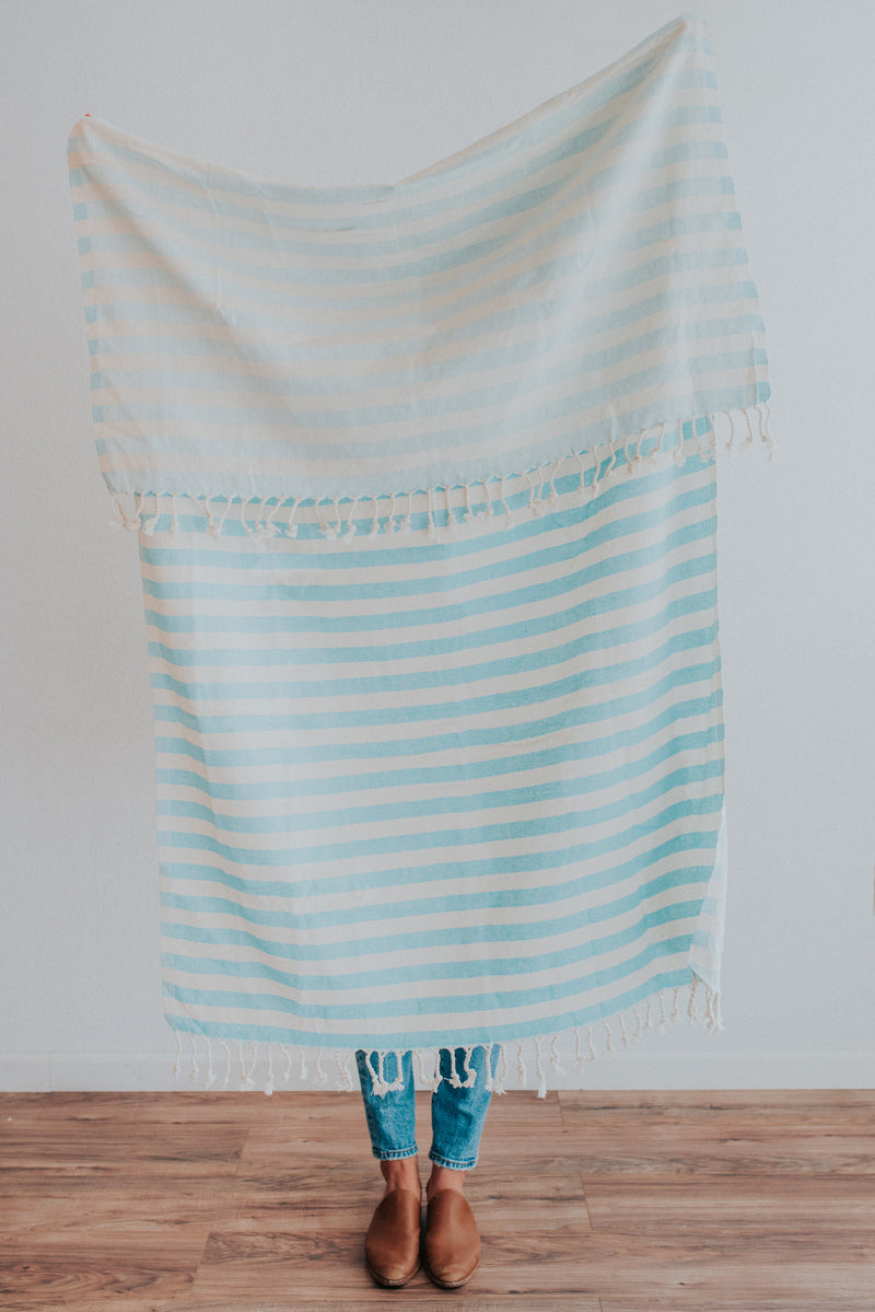 Person holding Bon Ton Studio Ulla Turkish Towel in Aqua color in front of wall