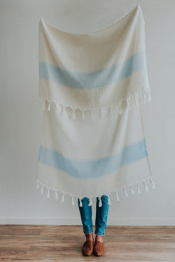 Person holding Bon Ton Studio Bodie Turkish Towel in Powder Blue color in front of wall