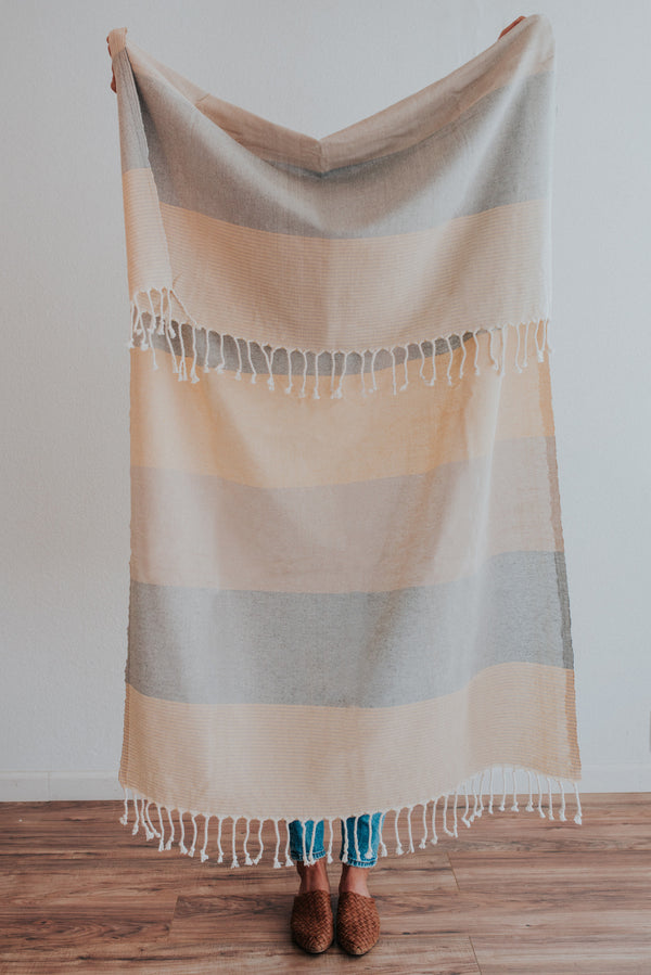 Person holding Bon Ton Studio Flora Turkish Towel in Caramel color in front of wall