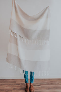 Person holding Bon Ton Studio Flora Turkish Towel in Flora Grey color in front of wall