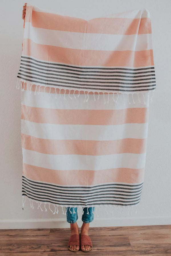 Person holding Bon Ton Studio Elvi Turkish Towel in Salmon color in front of wall
