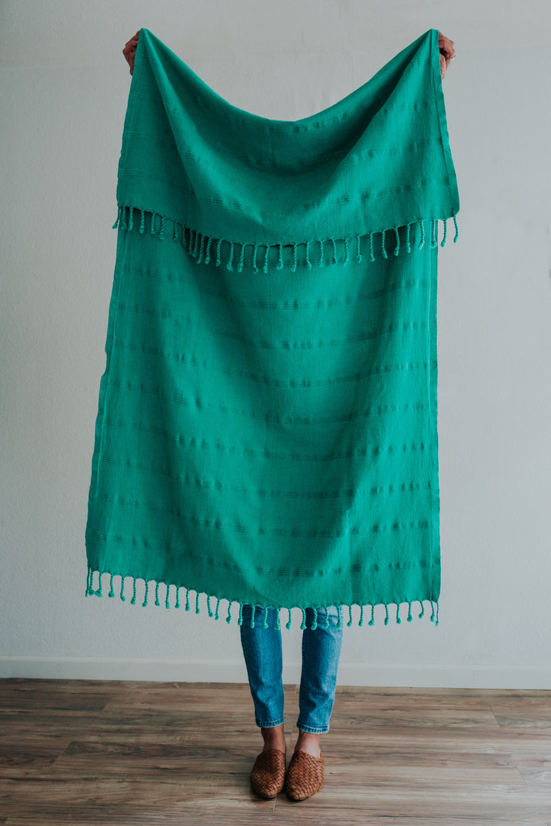 Person holding Bon Ton Studio Aggie Turkish Towel in Jade color in front of wall