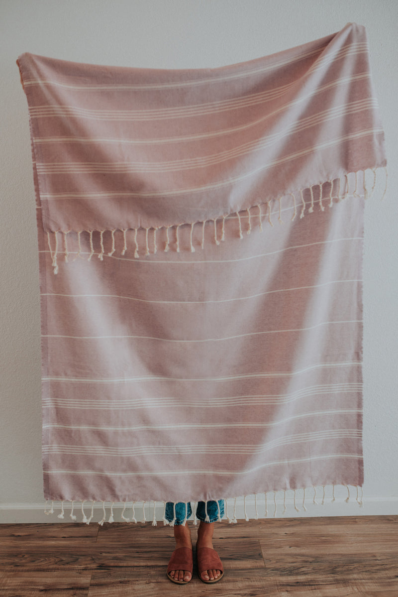 Person holding Bon Ton Studio Thea Turkish Towel in Lilac color in front of wall